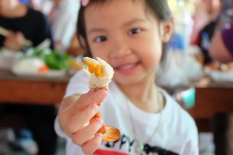 young child at crab feed holding up crab leg in front of the camera